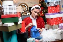 Hombre de negocios en la oficina en el ` s Eve del Año Nuevo Él lleva el traje de Santa Claus Alrededor de él muchos regalos, Fotografía de archivo
