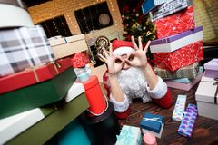 Hombre de negocios en la oficina en el ` s Eve del Año Nuevo Él lleva el traje de Santa Claus Alrededor de él muchos regalos, Fotos de archivo libres de regalías