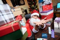 Hombre de negocios en la oficina en el ` s Eve del Año Nuevo Él lleva el traje de Santa Claus Alrededor de él muchos regalos, Imagen de archivo libre de regalías