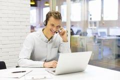 Hombre de negocios en la oficina en el teléfono con las auriculares, Skype Foto de archivo libre de regalías