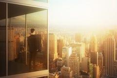 Hombre de negocios en la oficina moderna que mira la ciudad Imagen de archivo