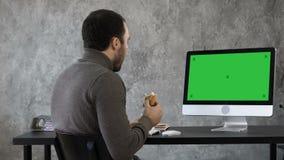Hombre de negocios en la oficina que desayuna, almuerzo y mirando algo en el mac, ordenador Maqueta verde de la pantalla almacen de metraje de vídeo