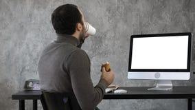Hombre de negocios en la oficina que desayuna, almuerzo y mirando algo en el mac, ordenador Visualización blanca imagen de archivo libre de regalías