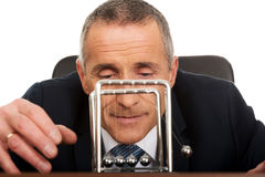 Hombre de negocios en la oficina que juega con las bolas del neutonio Fotos de archivo libres de regalías