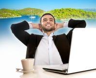 Hombre de negocios en la oficina que piensa y que sueña con vacaciones de verano Foto de archivo libre de regalías