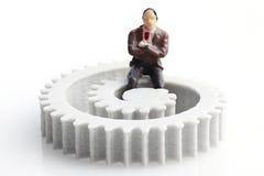 Hombre de negocios en la rueda dentada Foto de archivo libre de regalías