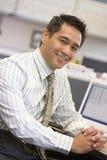Hombre de negocios en la sonrisa del cubículo imágenes de archivo libres de regalías