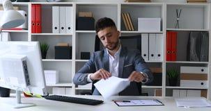 Hombre de negocios en la tabla en la lectura blanca de la oficina, rasgando y lanzando lejos los papeles