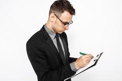 Hombre de negocios en los vidrios y el traje que sostienen una hoja de papel vacía, foto de archivo