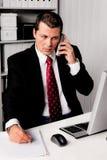 Hombre de negocios en oficina con el teléfono imágenes de archivo libres de regalías