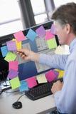 Hombre de negocios en oficina en el monitor con las notas sobre él Fotos de archivo libres de regalías