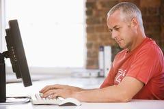 Hombre de negocios en oficina que pulsa en el ordenador Fotos de archivo