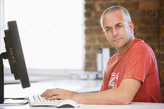Hombre de negocios en oficina que pulsa en el ordenador Foto de archivo