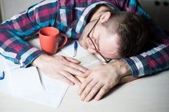 Hombre de negocios en paño casual que duerme en la tabla en oficina Imágenes de archivo libres de regalías