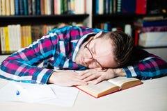 Hombre de negocios en paño casual que duerme en la tabla en oficina Foto de archivo libre de regalías