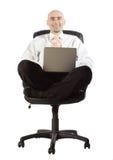 Hombre de negocios en silla con el ordenador portátil Imagen de archivo libre de regalías