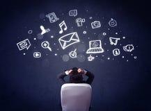 Hombre de negocios en silla con los iconos de las multimedias sobre su cabeza Imagen de archivo libre de regalías
