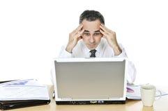 Hombre de negocios en su escritorio en el fondo blanco foto de archivo