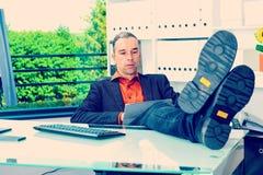 Hombre de negocios en su escritorio que se relaja con las piernas en el escritorio Imagen de archivo libre de regalías