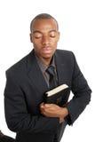 Hombre de negocios en sus rodillas que sostienen una biblia Imagen de archivo libre de regalías