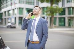 Hombre de negocios en traje azul que camina abajo de la calle Fotografía de archivo libre de regalías