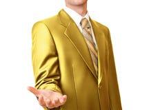 Hombre de negocios en traje del oro que gesticula con la mano vacía Fotos de archivo libres de regalías