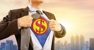 Hombre de negocios en traje del super héroe con la muestra de dólar Imagenes de archivo
