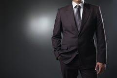 Hombre de negocios en traje en fondo gris Fotos de archivo