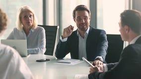 Hombre de negocios en traje que habla con los hombres de negocios que se sientan en la tabla almacen de metraje de vídeo