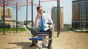Hombre de negocios en un campo de deportes al aire libre El concepto de una forma de vida sana almacen de metraje de vídeo