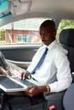 Hombre de negocios en un coche con la computadora portátil Imagen de archivo libre de regalías