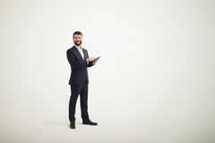 Hombre de negocios en un desgaste formal con el teléfono negro en sus manos Fotos de archivo