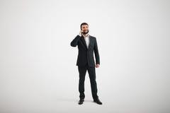 Hombre de negocios en un desgaste formal que habla por el teléfono Imagen de archivo libre de regalías