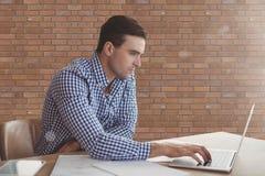 Hombre de negocios en un escritorio usando un ordenador contra la pared de ladrillo Imágenes de archivo libres de regalías