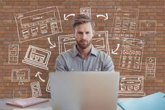 Hombre de negocios en un escritorio usando un ordenador contra la pared de ladrillo con los gráficos Foto de archivo libre de regalías