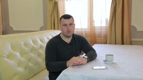 Hombre de negocios en un restaurante que habla con la cámara metrajes