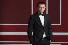 Hombre de negocios en un traje en una pared roja Foto de archivo libre de regalías