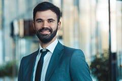 Hombre de negocios en un traje fromal en un primer feliz sonriente del centro de negocios foto de archivo