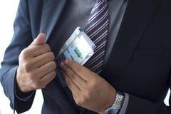 Hombre de negocios en un traje que encubre 100 cuentas de los lenguados, concepto peruano de la moneda imagenes de archivo