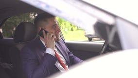 Hombre de negocios en un traje que habla en el teléfono en coche metrajes