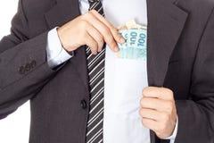 Hombre de negocios en un traje que pone el dinero en su bolsillo Imagen de archivo libre de regalías
