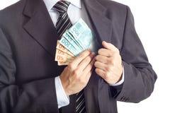 Hombre de negocios en un traje que pone el dinero en su bolsillo Fotografía de archivo libre de regalías