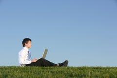 Hombre de negocios en una computadora portátil Imágenes de archivo libres de regalías