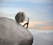 Hombre de negocios en una roca Foto de archivo