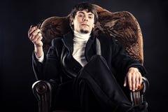 Hombre de negocios en una silla con un tubo Fotos de archivo libres de regalías