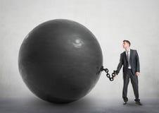 Hombre de negocios encadenado a una bola grande imagen de archivo libre de regalías