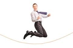 Hombre de negocios encantado que salta sobre una cuerda Foto de archivo libre de regalías