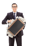 Hombre de negocios encantado que sostiene una cartera llena de dinero Imágenes de archivo libres de regalías