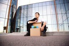 Hombre de negocios encendido que se sienta en la calle Imagenes de archivo