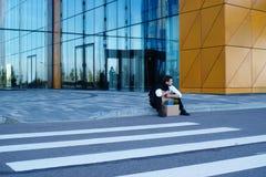 Hombre de negocios encendido que se sienta en la calle Imagen de archivo